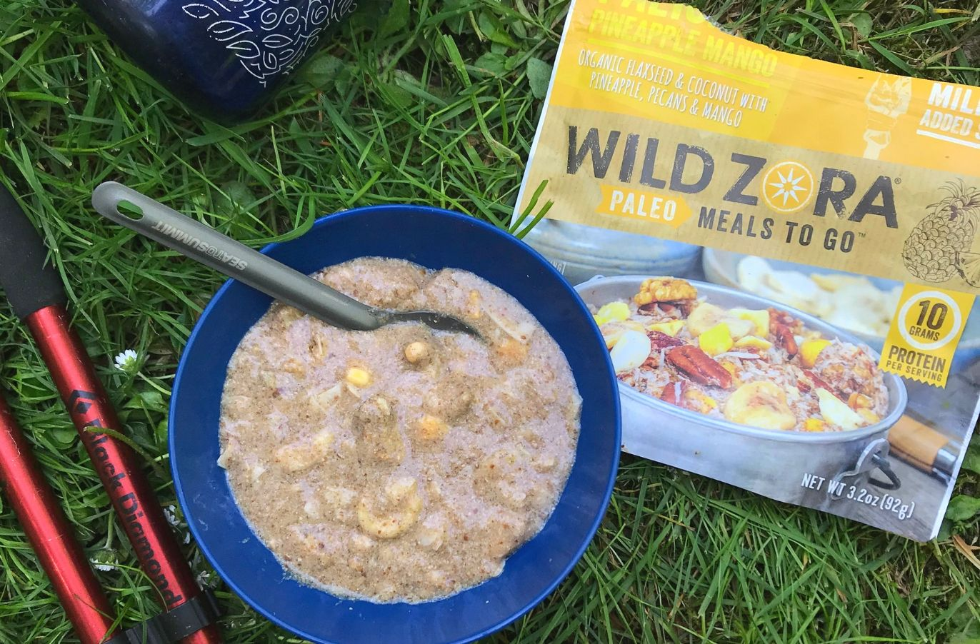 Wild Zora paleo meals to go package beside a bowl of paleo porridge on a grassy surface