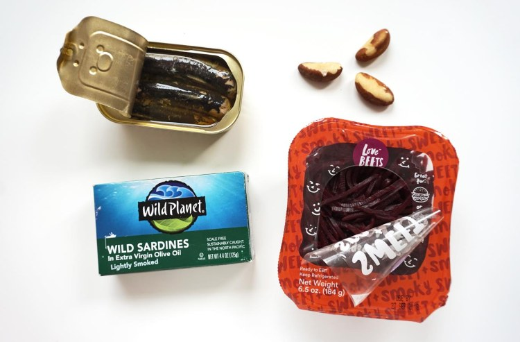open can of sardines above a wild plant wild sardines box next to 3 brazil nuts and a container of love beets shredded beets