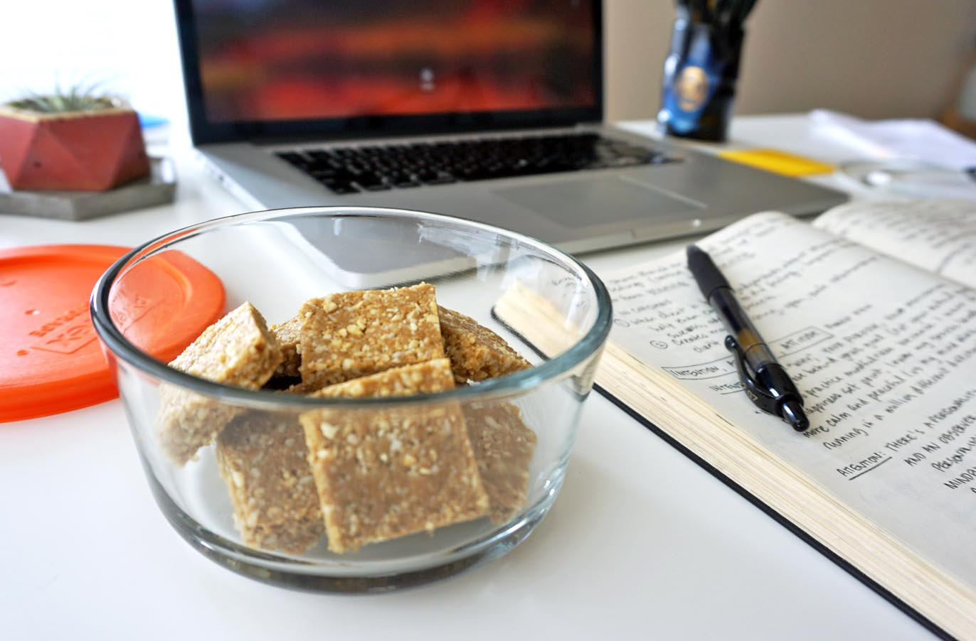 ginger turmeric bone broth protein bites in a glass container next to an open notebook and a computer