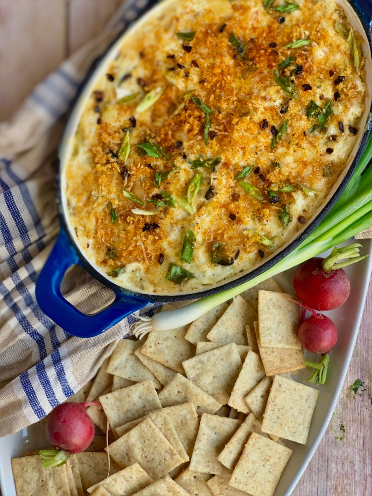 bowl of bubbly artichoke dip surrounded by crackers green onion and turnips