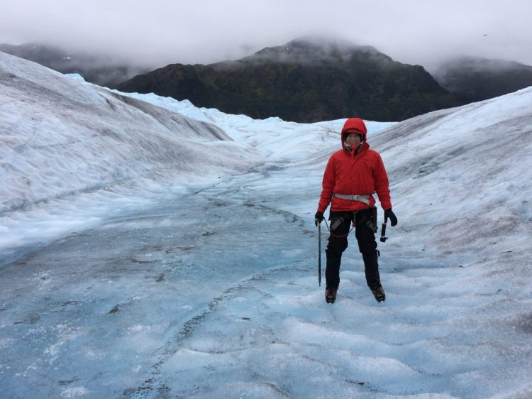 woman in red jacket standing on a glacier in alaska