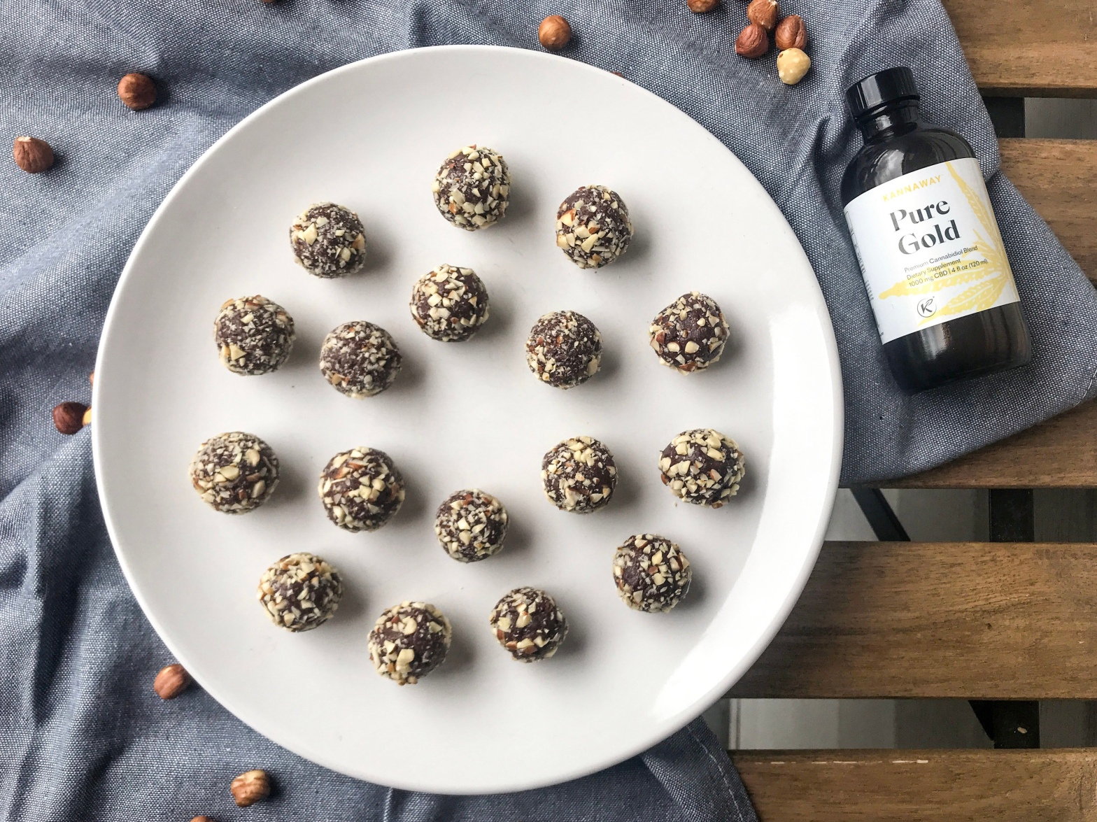 chocolate hazelnut cbd dessert balls on a plate next to a bottle of kannaway pure gold cbd oil