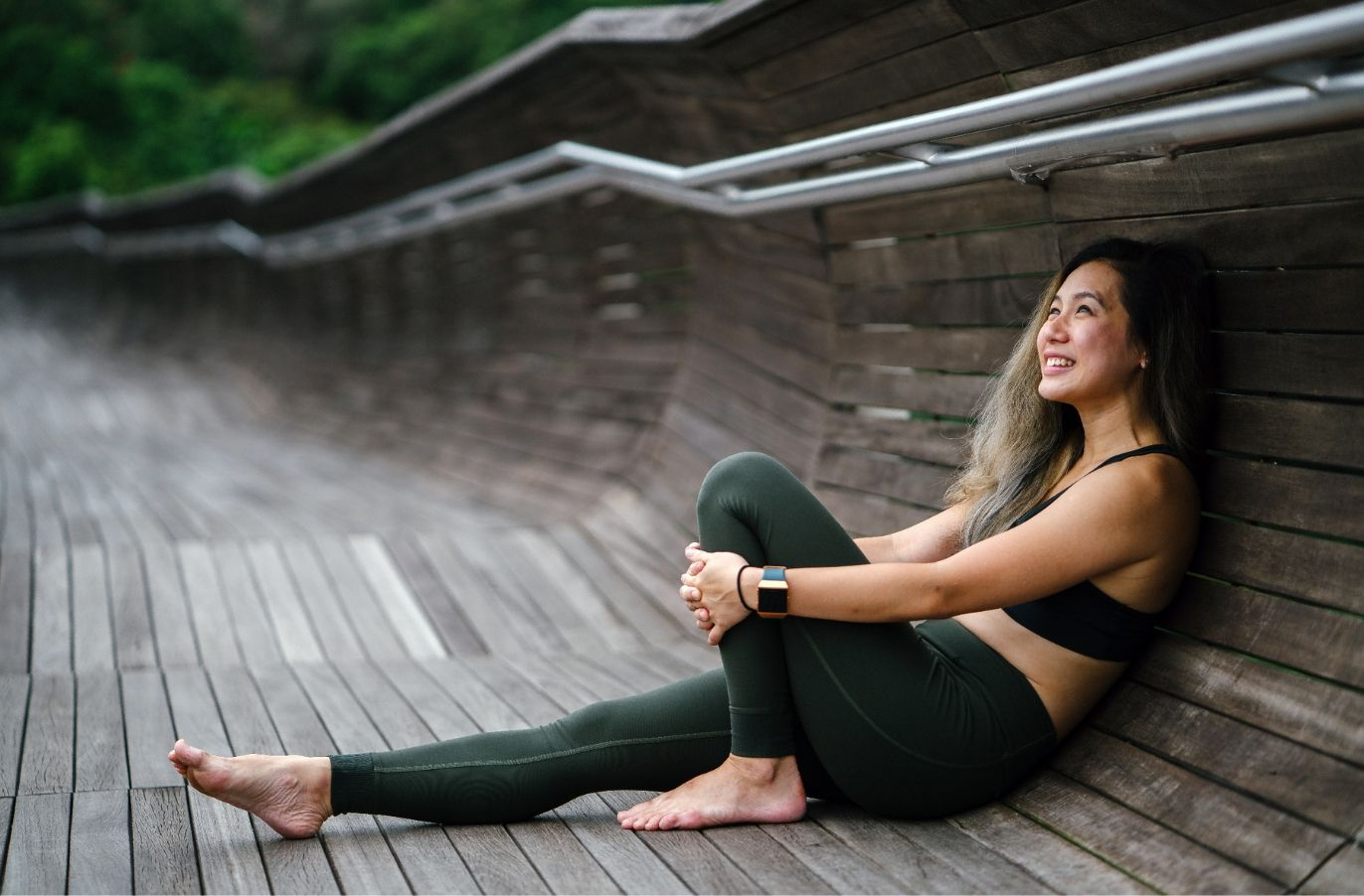 woman in sports bra and legging leaning against a wooden walkway smiling and holding her knee