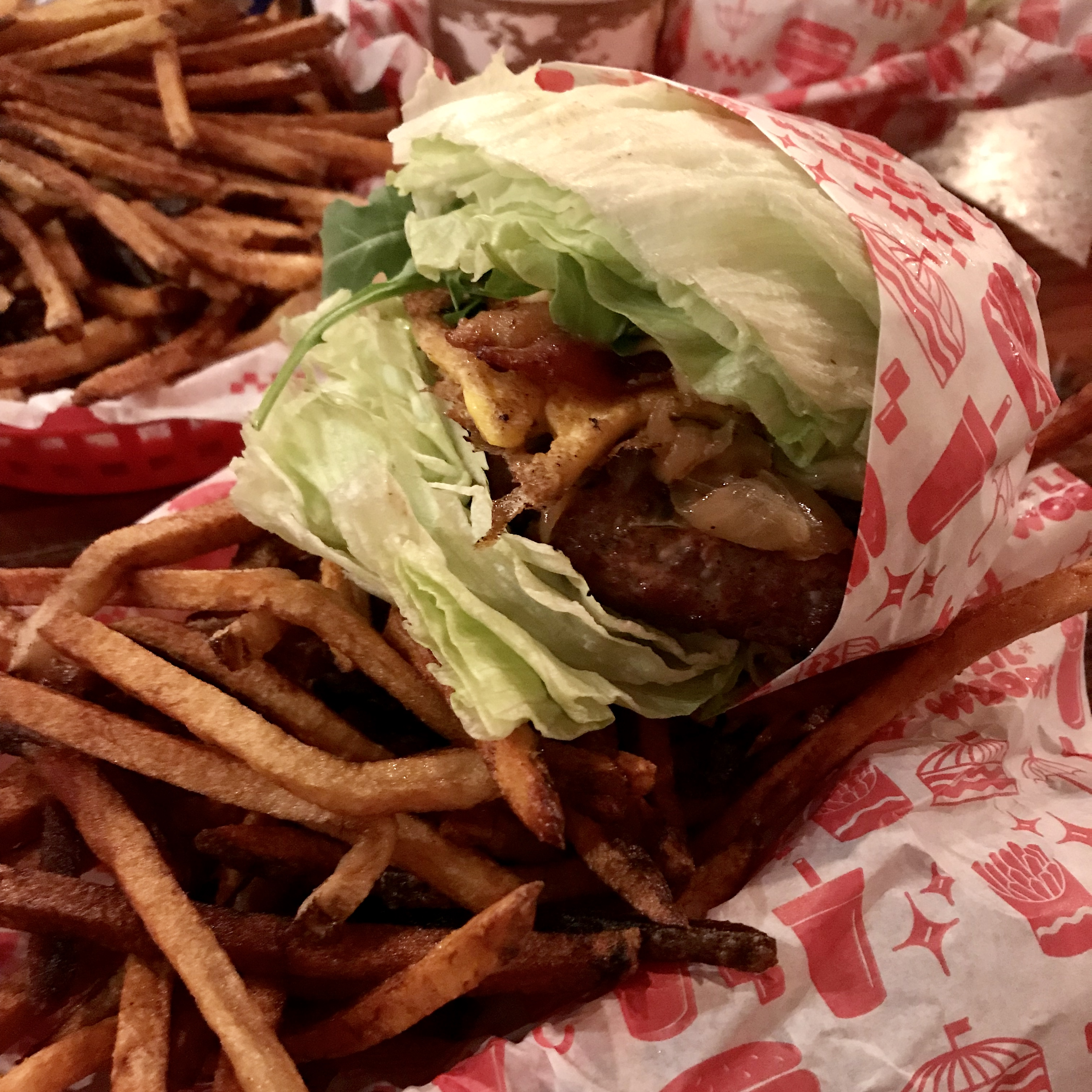 a lettuce wrap grass-fed burger with french fries at lil woodys