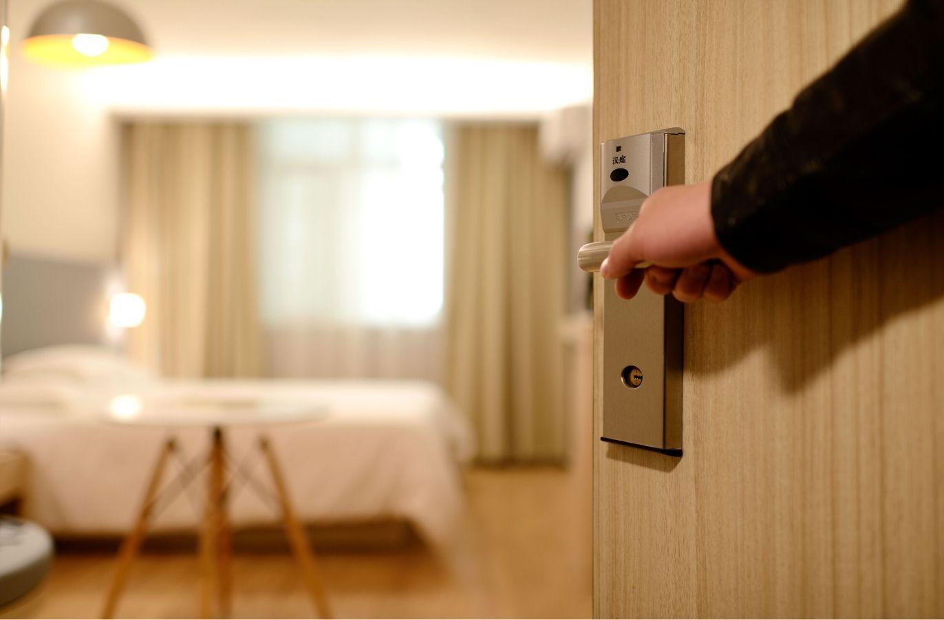 hand opening door into modern hotel room with bed
