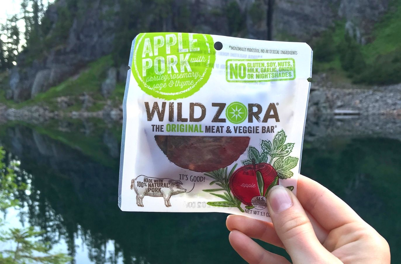 hand holding up an apple pork Wild Zora original meat and veggie bar