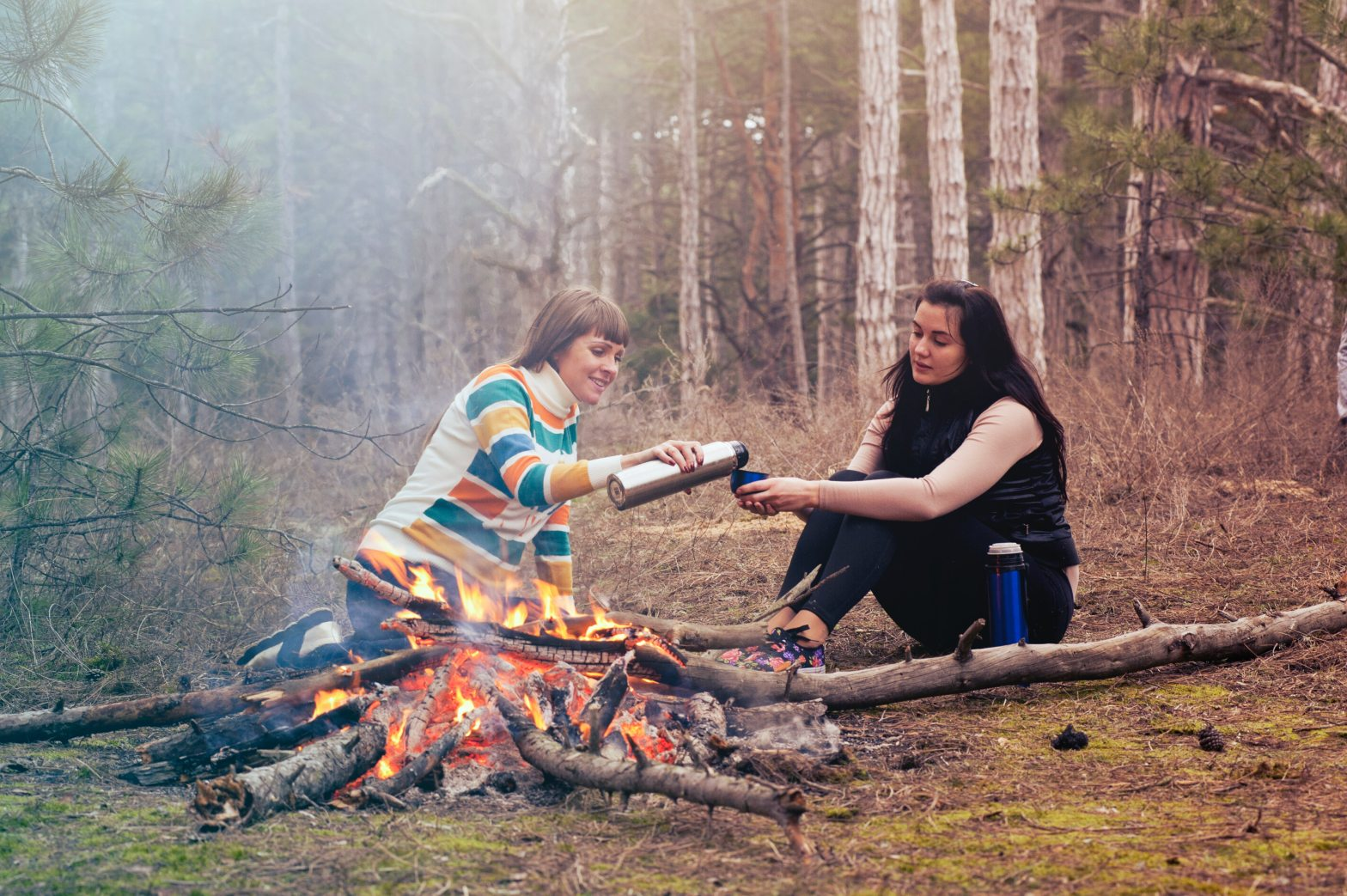 two women smiling sharing a drink beside a campfire
