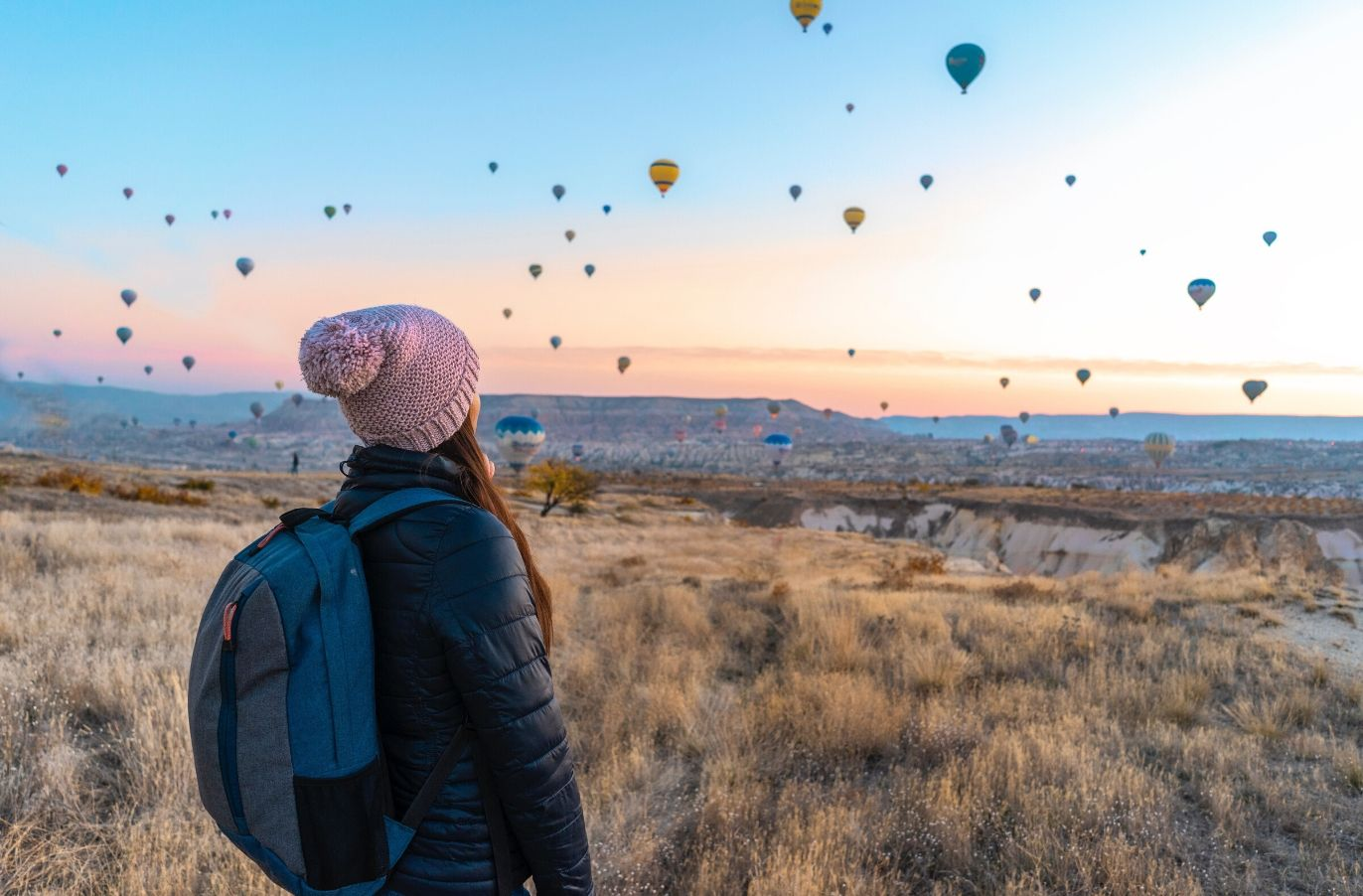 woman in winter cloths looking into the distance at hot air balloons