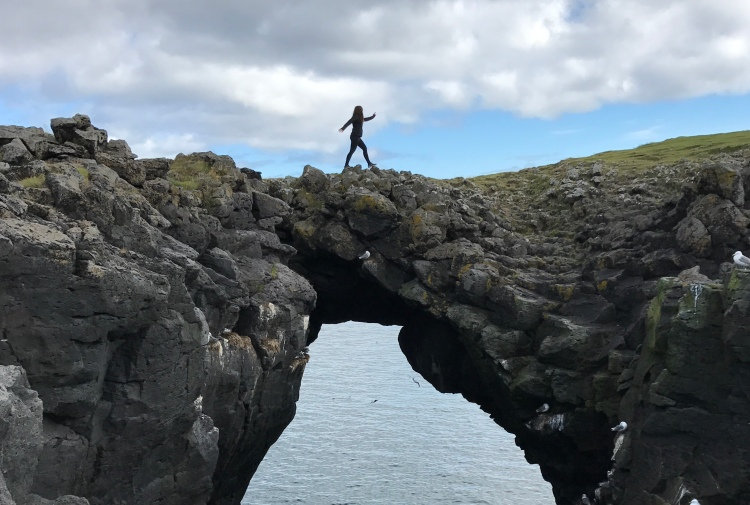 woman walking over a natural land bridge in iceland