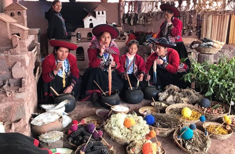four peruvian women in traditional peruvian costume dying yarn