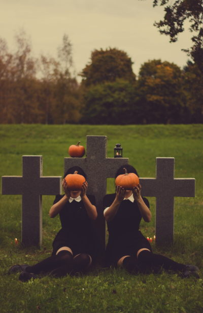 spooky girls with pumpkins in cemetary