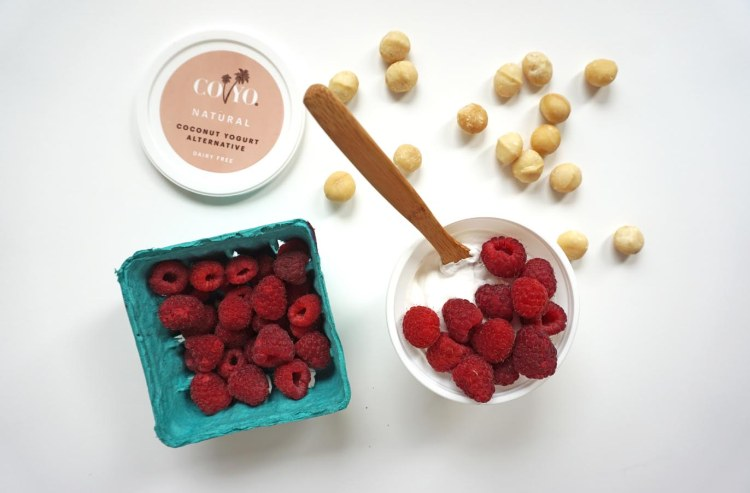 container of coyo with raspberries beside a container of raspberries beside macadamia nuts