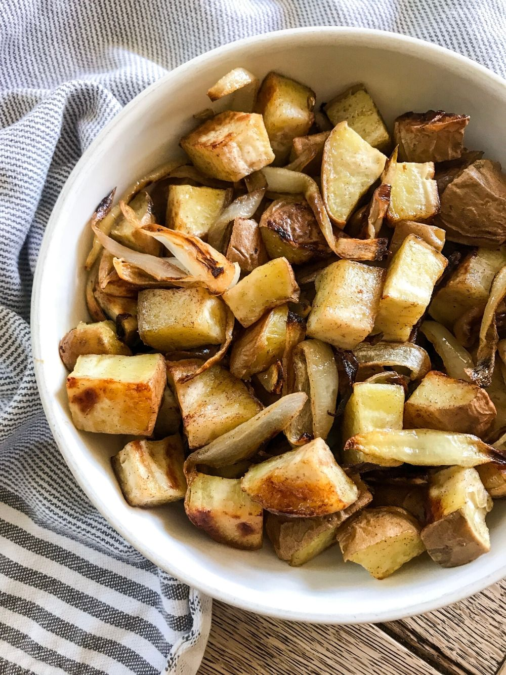 a white bowl of paleo roasted cinnamon white sweet potatoes and onion on a blue striped dish towel