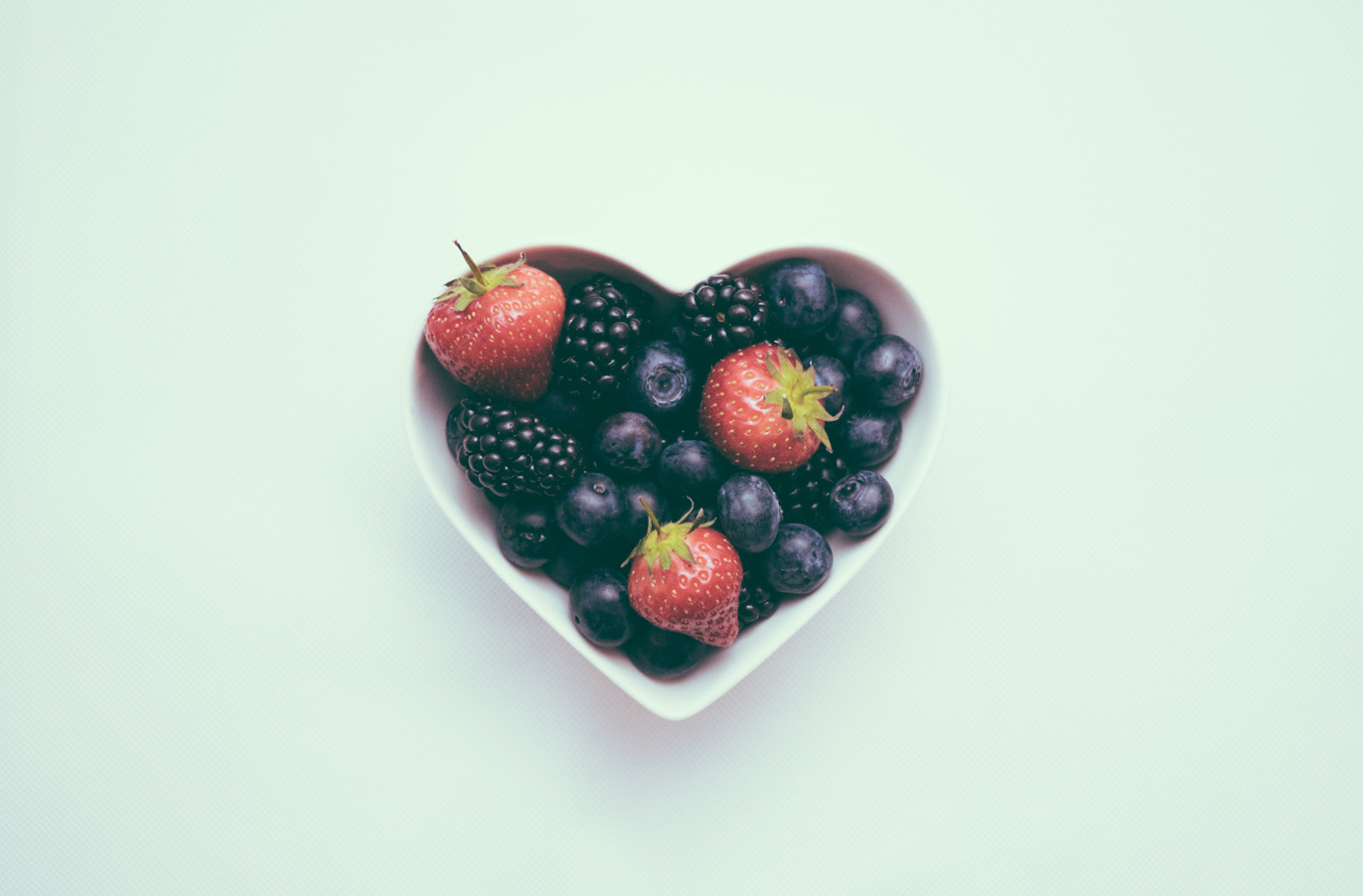 berries in a heart shaped bowl on a teal background