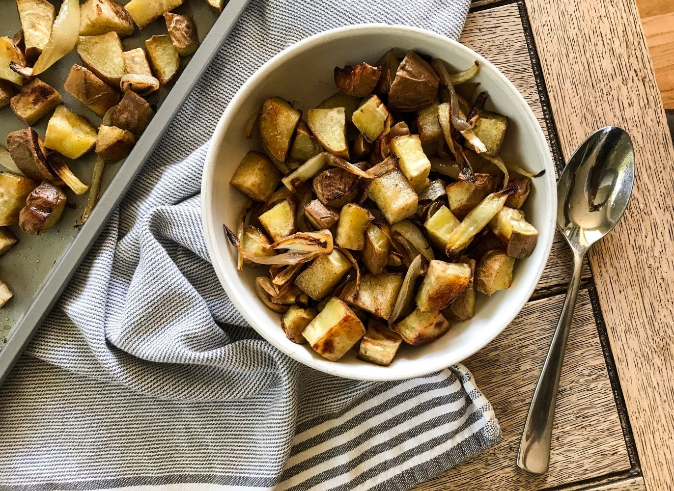 a white bowl of paleo roasted cinnamon white sweet potatoes and onion on a blue striped dish towel beside a metal spoon