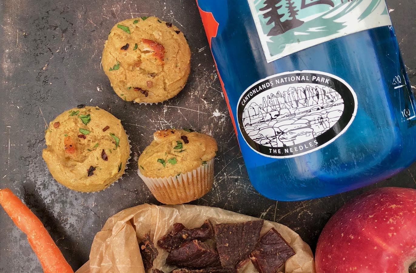 paleo green chili chicken mini snack muffins next to a water bottle and trail snacks