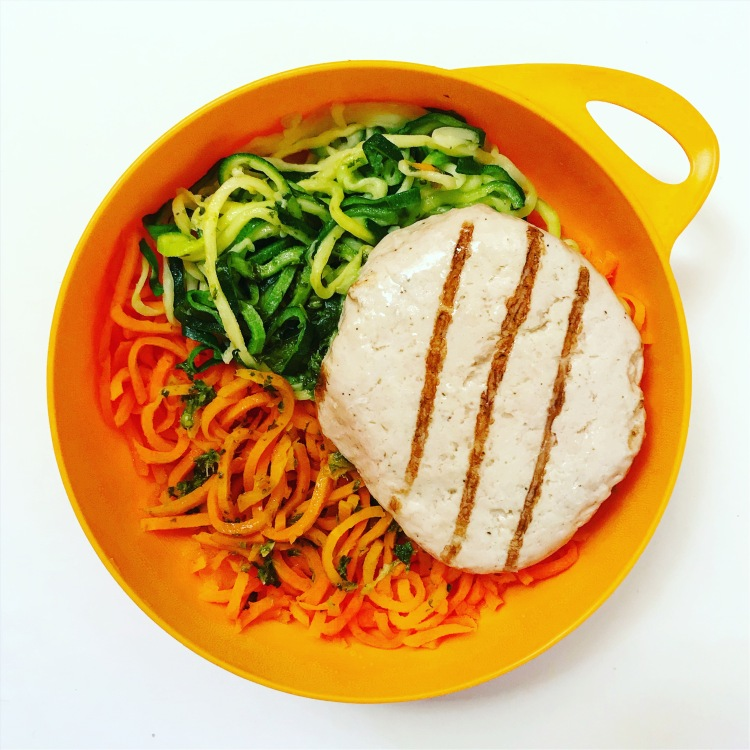 zucchini noodles spiralized carrot with coconut oil and chopped basil and a trader joe's roasted chicken patty