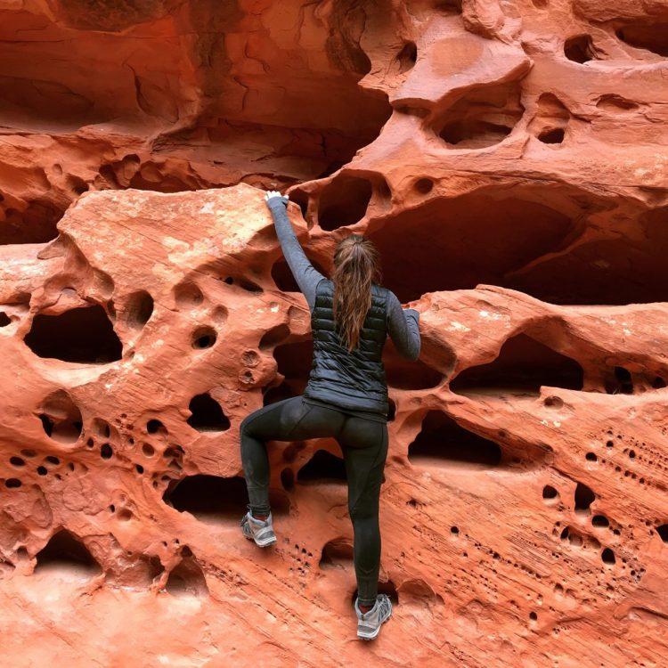 woman climbing red rock cliff face
