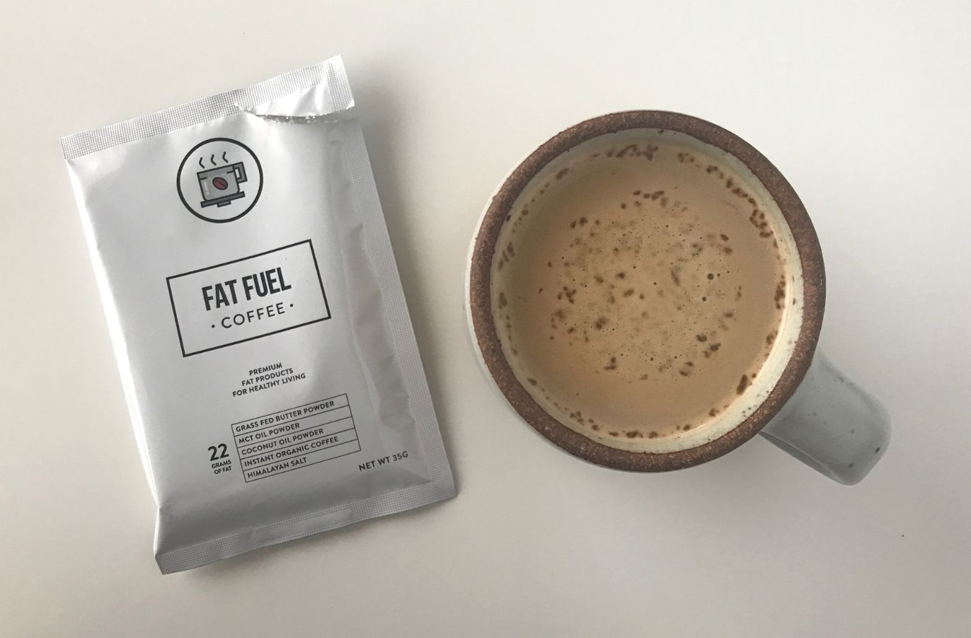 a packet of fat fuel coffee next to a mug of Keto Coffee on a white surface