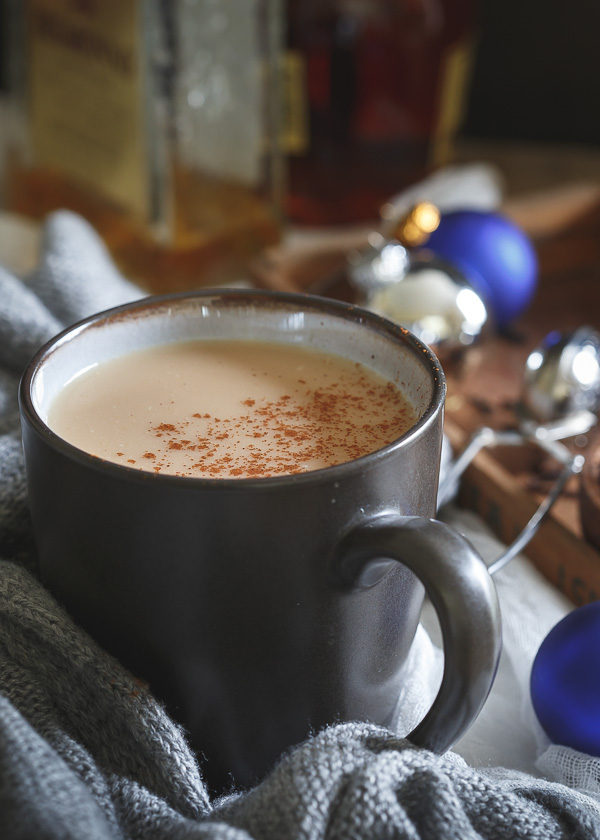 black mug with hot toddy and cinnamon