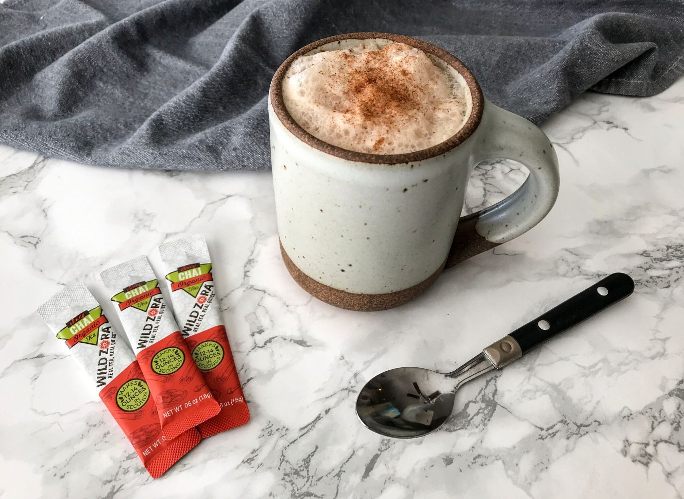 easy chai latte recipe in a ceramic mug beside three packets of wild zora spicy chai tea and a spoon with a black handle