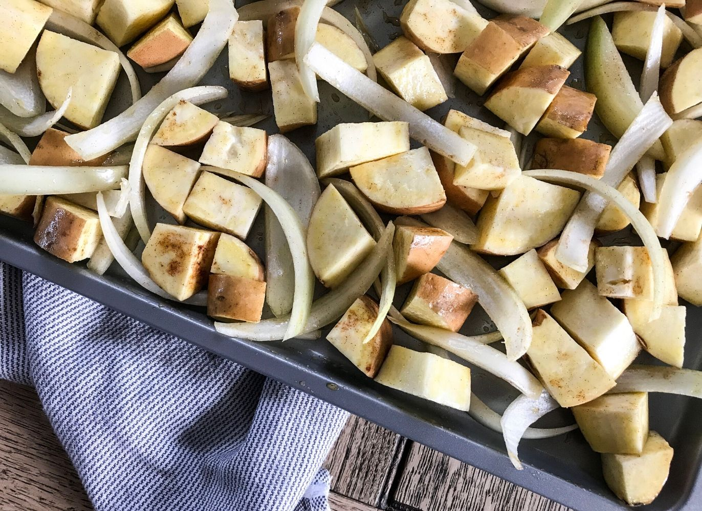 a white bowl of cinnamon white sweet potatoes and onion on a blue striped dish towel