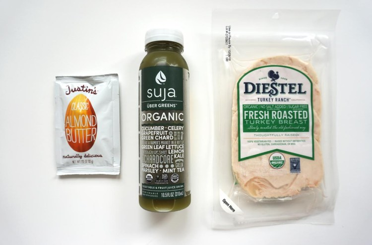 justins almond butter packet beside bottle of suja uber greens juice beside a packet of diestel turkey