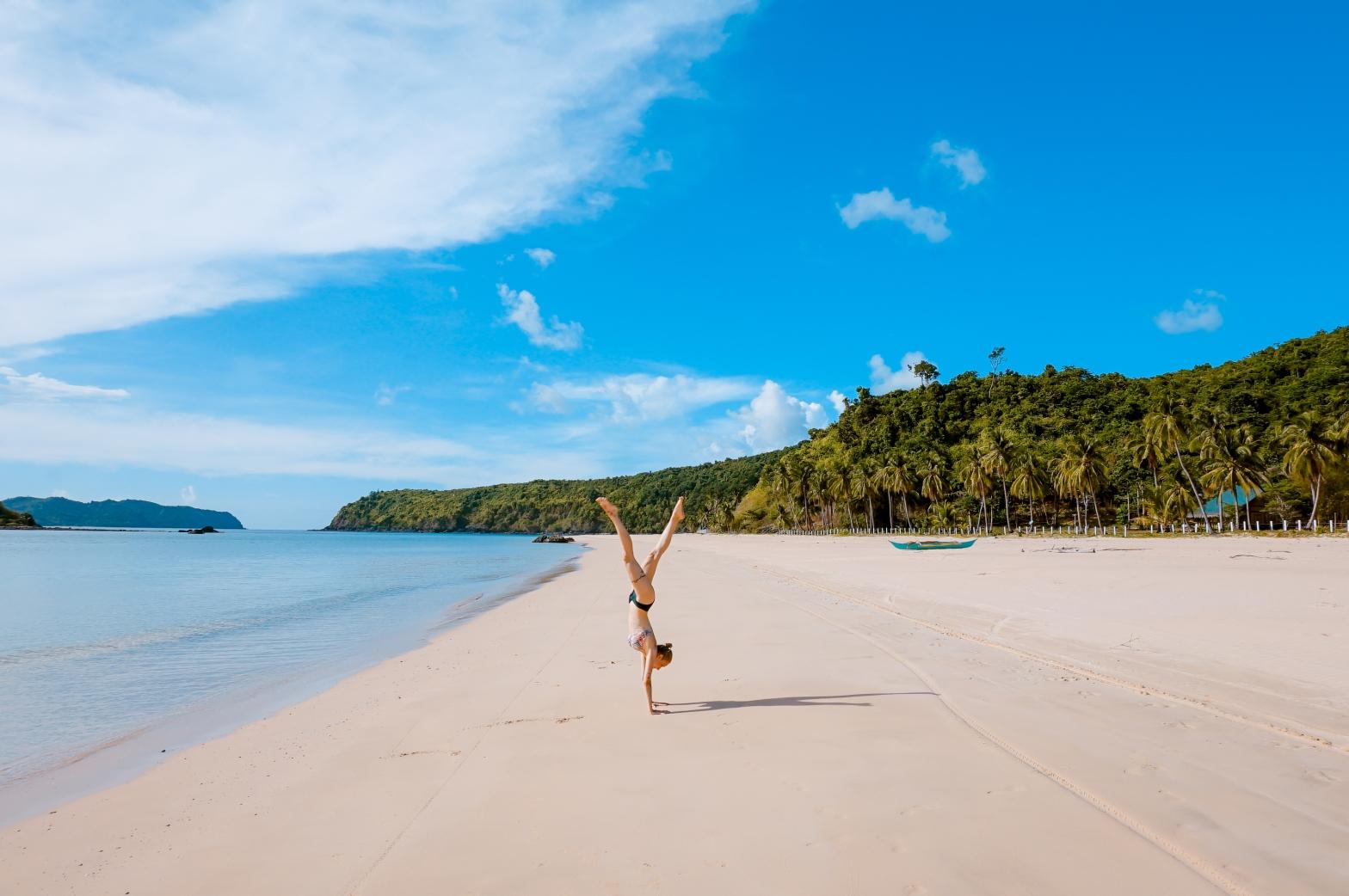 woman in bikini doing handstand on a tropical beach