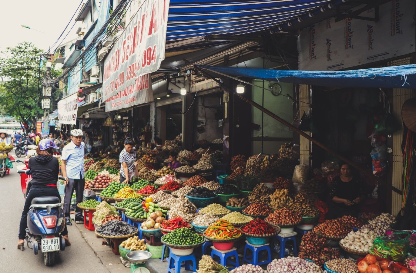 foreign market stall with trays of fruits and vegetables